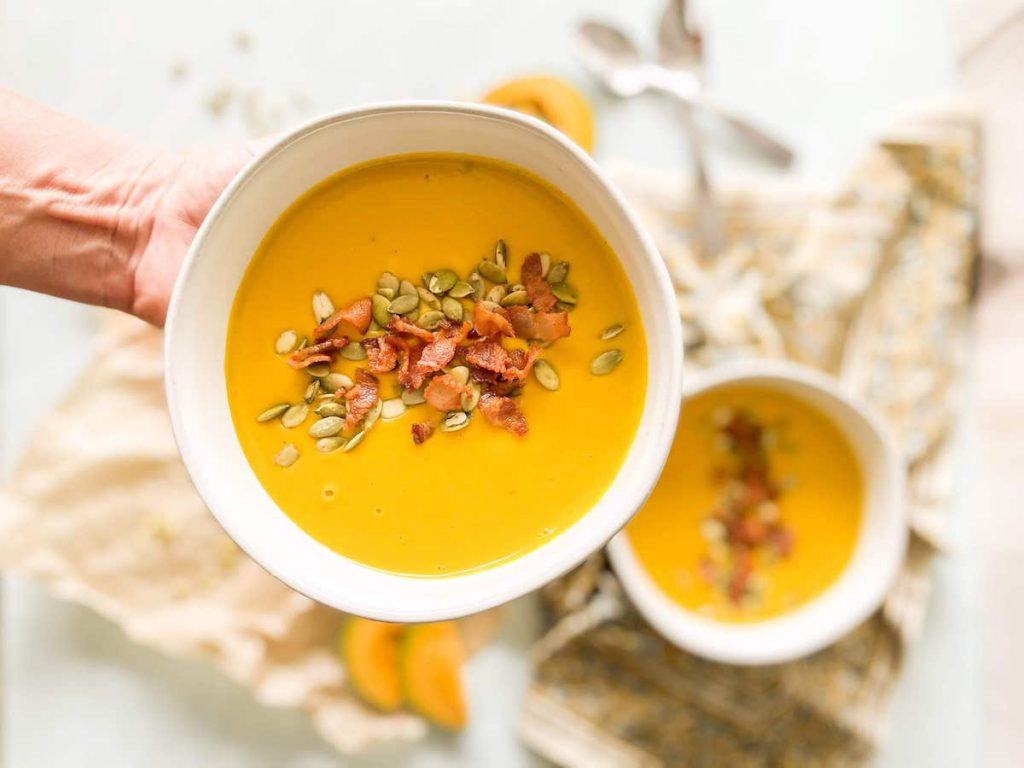 Roasted Kabocha Squash Soup Served in bowl with pumpkin seeds and bacon